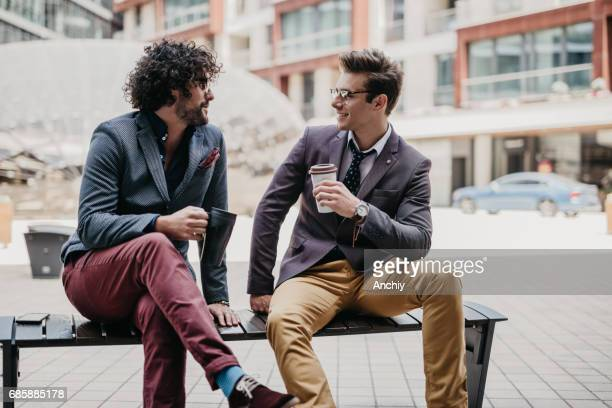 Geschäftsleute, die auf der Bank sitzen nehmen eine Kaffeepause