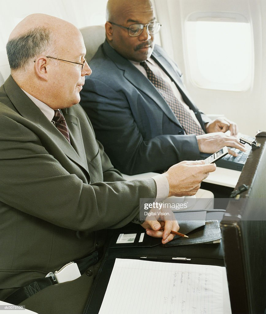 Businessmen Sitting Side by Side in an Aircraft : Stock Photo
