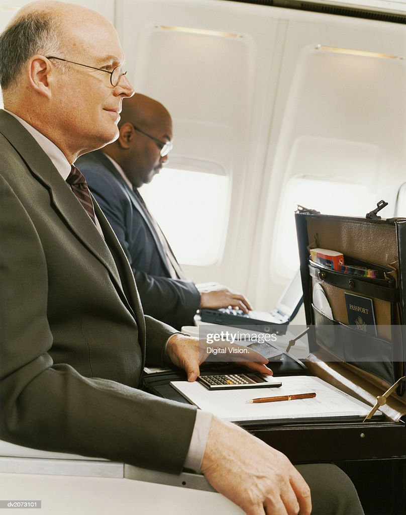 Businessmen Sitting Side by Side in an Aircraft With Open Briefcase and Laptop : Stock Photo