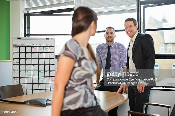 businessmen smiling at woman in conference room - compassionate eye foundation stock pictures, royalty-free photos & images