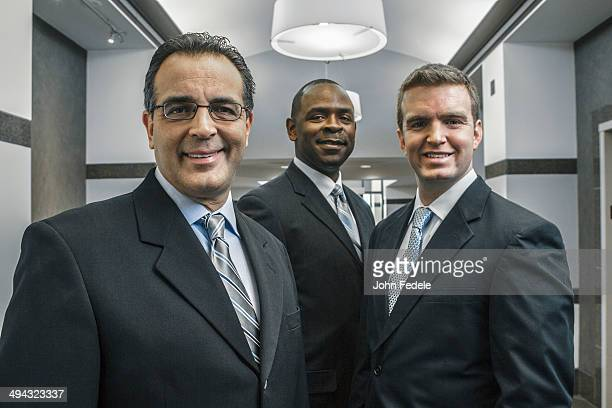 Businessmen smiling in office corridor
