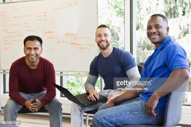 Businessmen smiling in office meeting