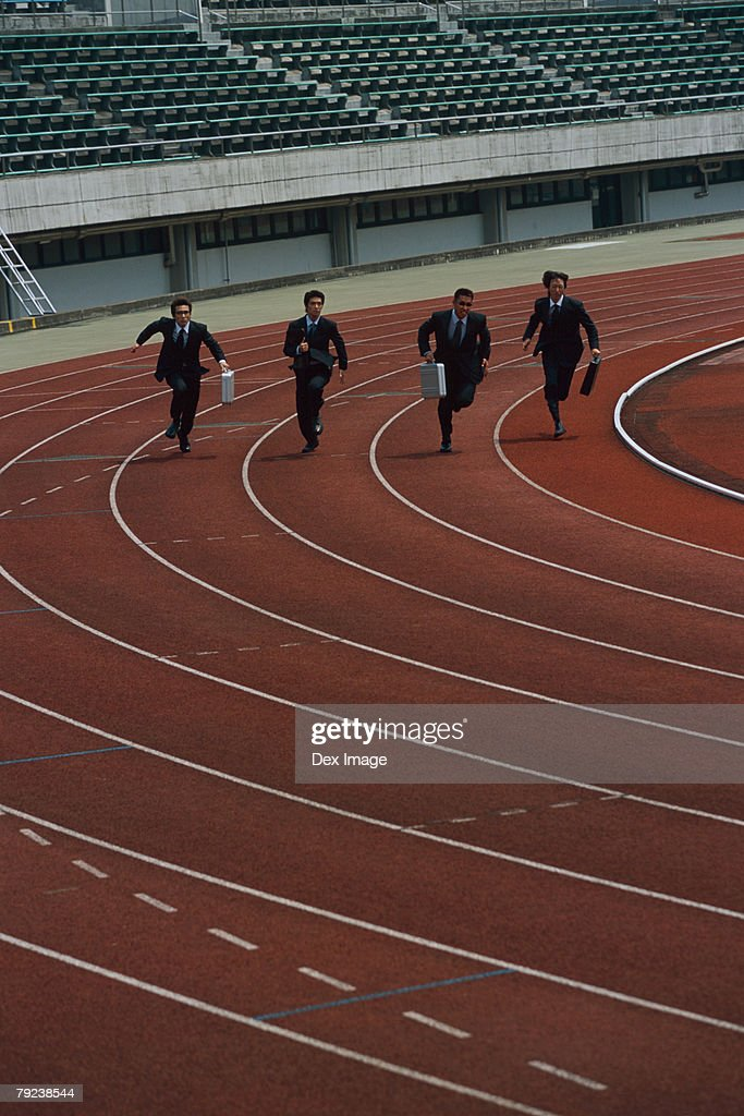Businessmen sprinting, carrying briefcases : Stock Photo