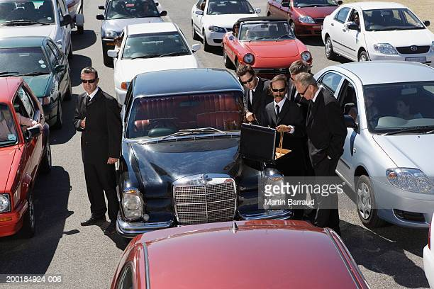 Businessmen standing amongst traffic jam, looking in briefcase