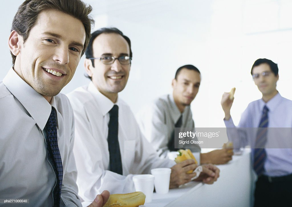 Businessmen standing around counter with food and drinks : Stockfoto