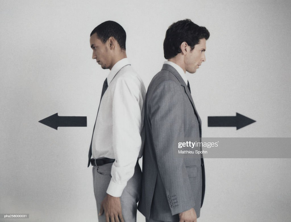 Businessmen standing back to back with arrow signs pointing in opposite directions : Stockfoto