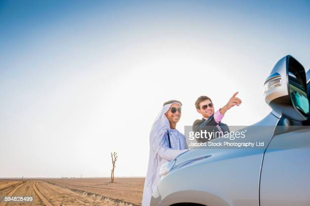 Businessmen standing in desert