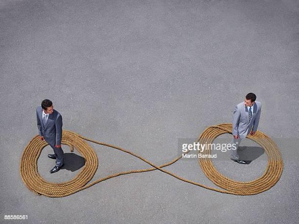 Businessmen standing in rope infinity symbol