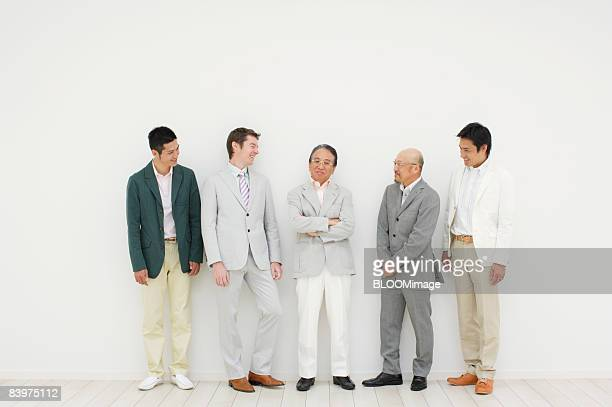 Businessmen standing in row against wall, talking