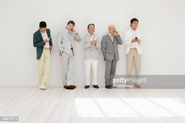 Businessmen standing in row against wall, using cellular phone