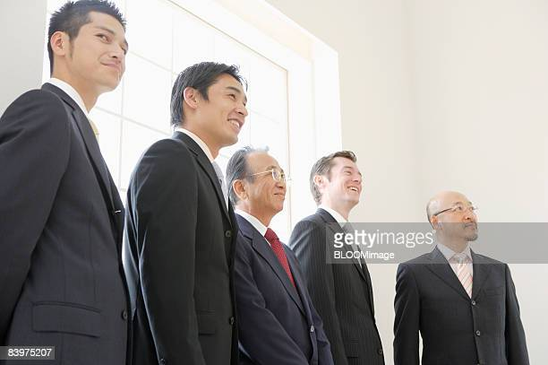 Businessmen standing in row against widow, low angle view