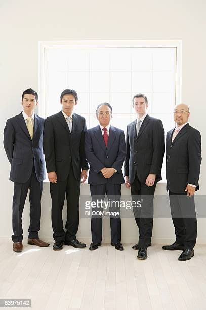 Businessmen standing in row against window