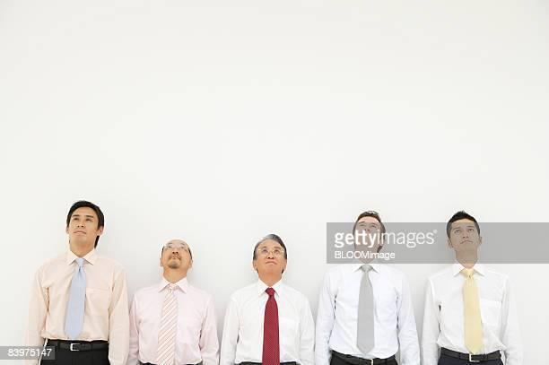 Businessmen standing in row, looking upward
