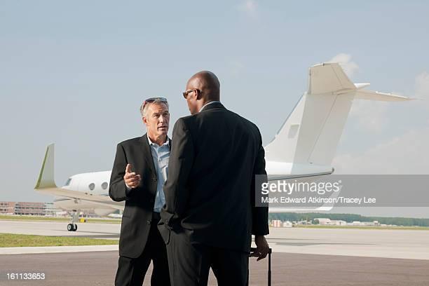 Businessmen standing on airport tarmac