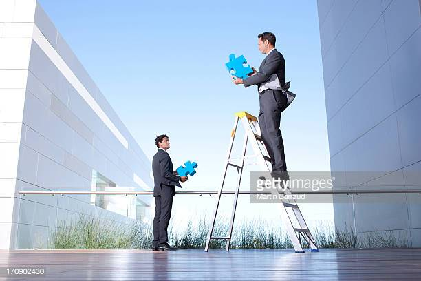 Businessmen standing on balcony holding jigsaw puzzle pieces