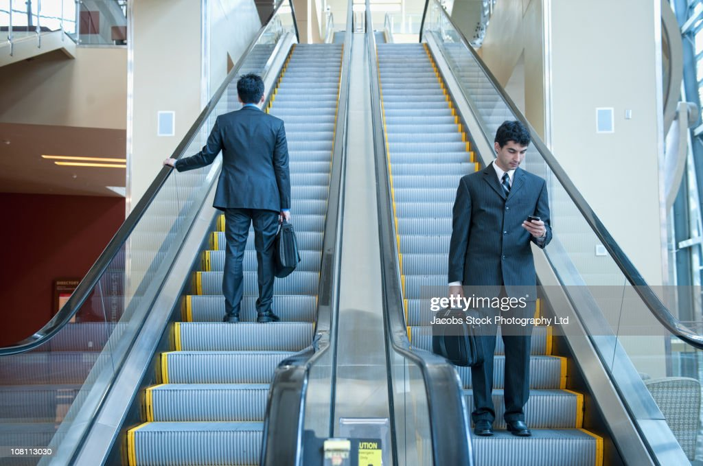 Businessmen standing on escalators : Stock Photo
