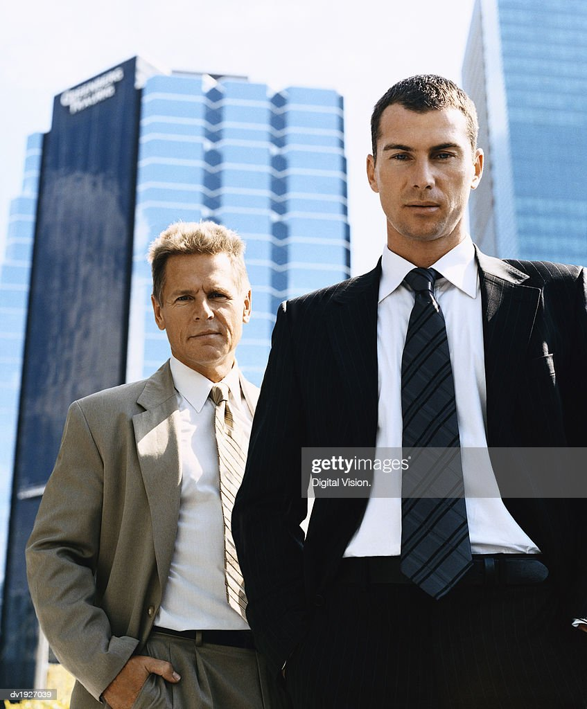 Businessmen Standing Outdoors in a City Wearing Full Suits : Stock Photo