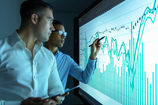Businessmen studying graphs on an interactive screen in business meeting - gettyimageskorea