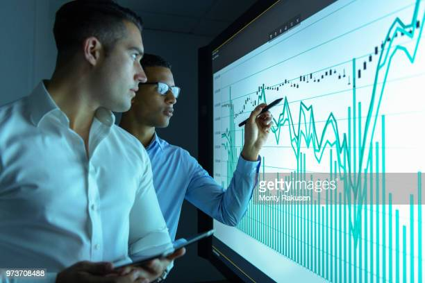 businessmen studying graphs on an interactive screen in business meeting - onderzoek stockfoto's en -beelden