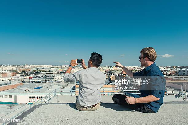 Businessmen taking photograph with smartphone on roof terrace, Los Angeles, California, USA