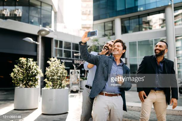 businessmen taking selfie together after work outside office - smart casual stock pictures, royalty-free photos & images
