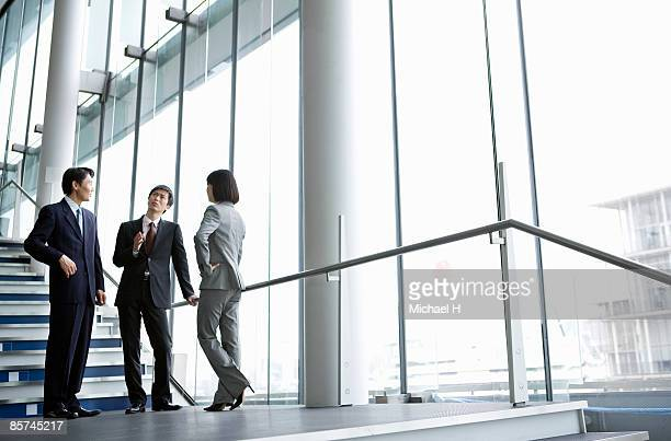 Businessmen talk by the staircase landing.