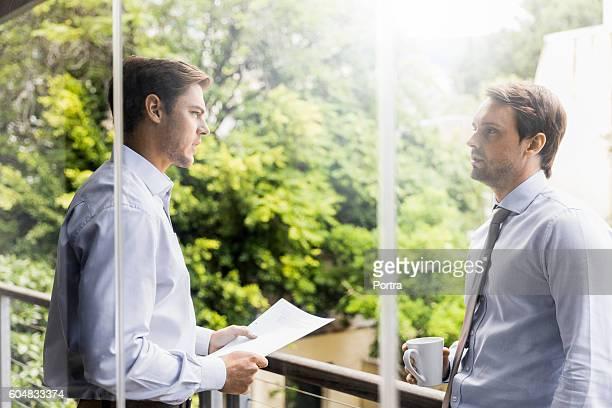 Businessmen talking at balcony seen through glass
