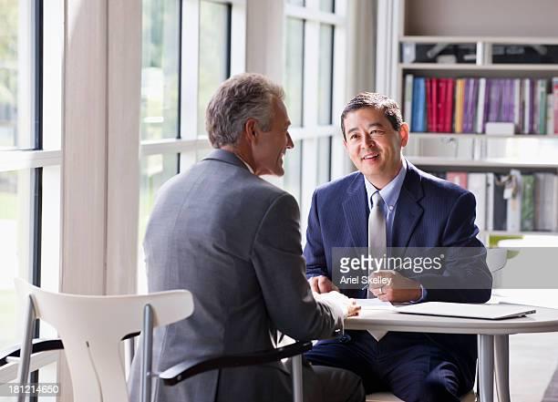Businessmen talking at desk