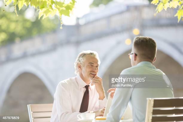 Businessmen talking at sidewalk cafe