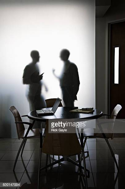 Businessmen Talking Behind Frosted Glass Wall