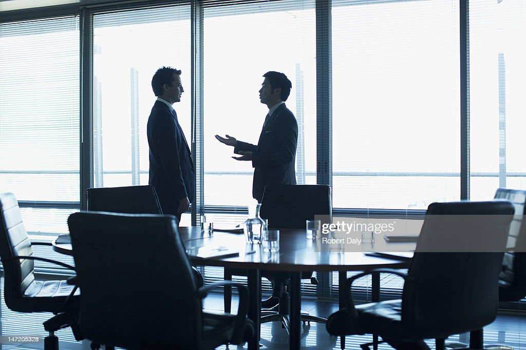 Businessmen talking face to face in conference room : Stock Photo