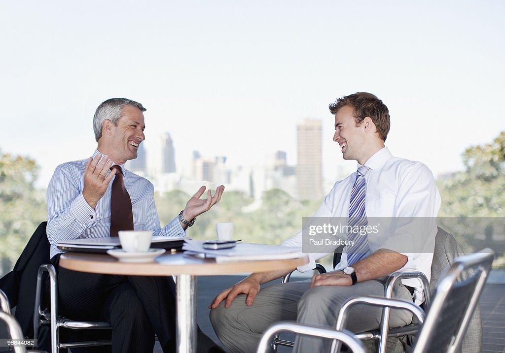 Businessmen talking in cafe : Stock Photo