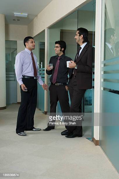 Businessmen talking in office corridor