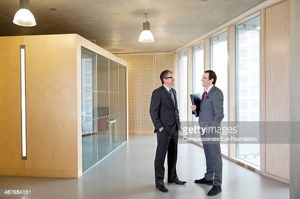 businessmen talking in office hallway - formelle geschäftskleidung stock-fotos und bilder