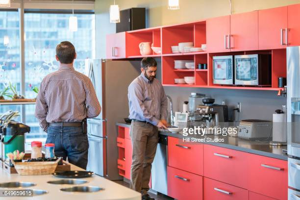 Businessmen talking in office kitchen