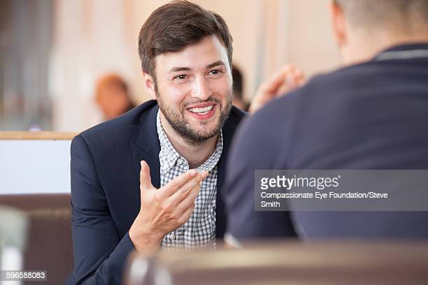Businessmen talking in waiting area at airport