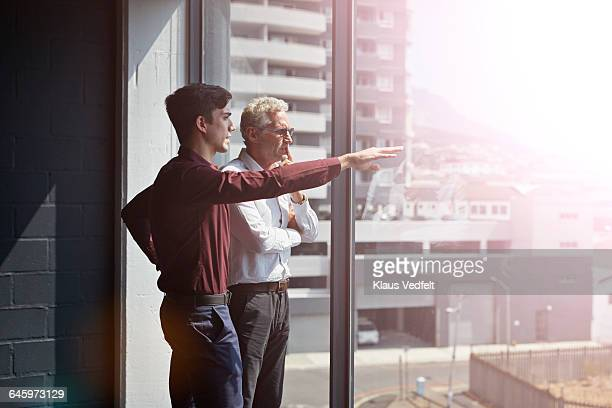 Businessmen talking & looking out of window