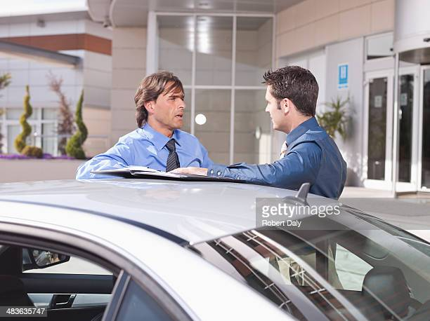 businessmen talking near car - approaching stock pictures, royalty-free photos & images