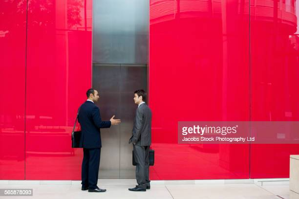 businessmen talking near office elevator - red suit stock pictures, royalty-free photos & images