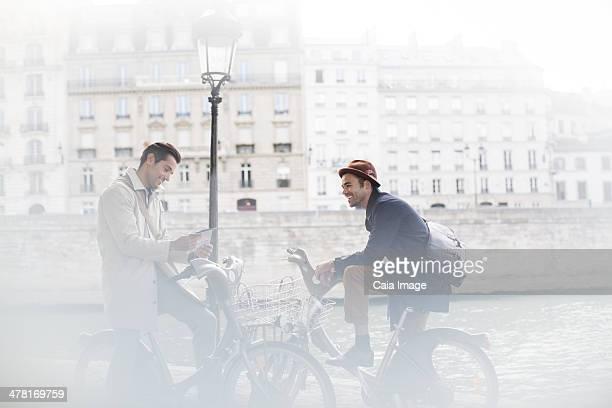 Businessmen talking on bicycles along Seine River, Paris, France