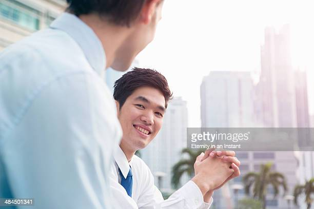 Businessmen talking outdoors.