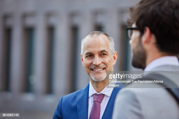 """businessmen talking outdoors - """"compassionate eye"""" stock pictures, royalty-free photos & images"""