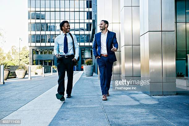 businessmen talking outside office building - gemeinsam gehen stock-fotos und bilder