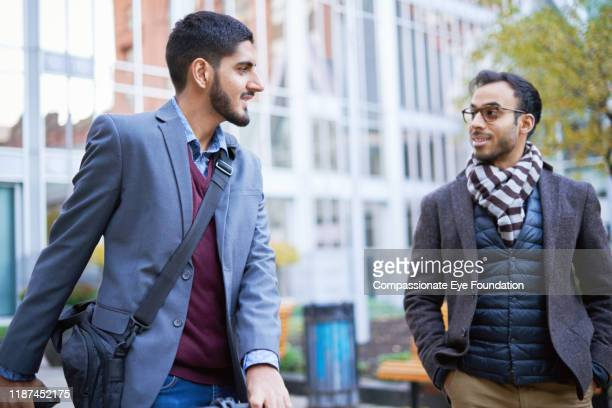 businessmen talking pushing bicycle in city - striped blazer stock pictures, royalty-free photos & images