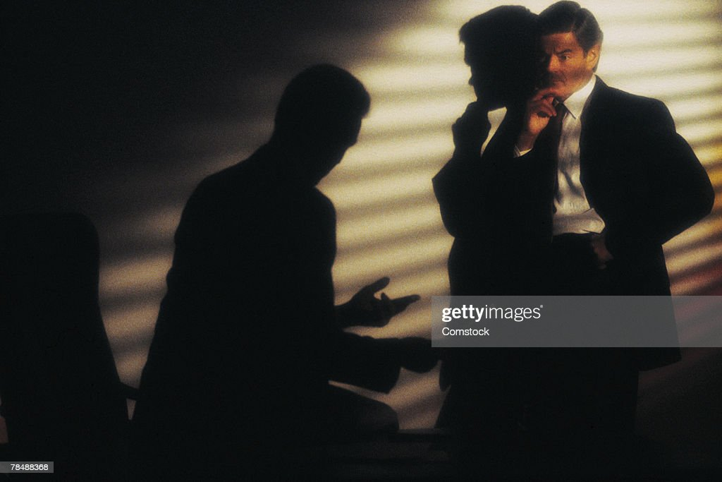 Businessmen talking secretively : Stock Photo