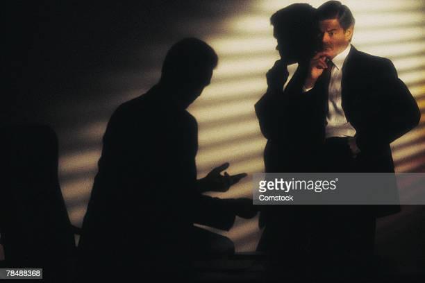 Businessmen talking secretively