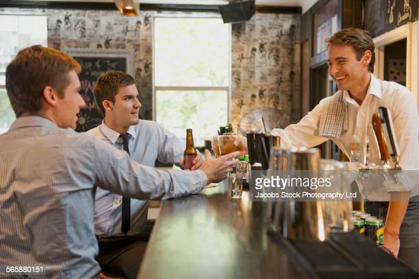 Businessmen talking to bartender and drinking at bar