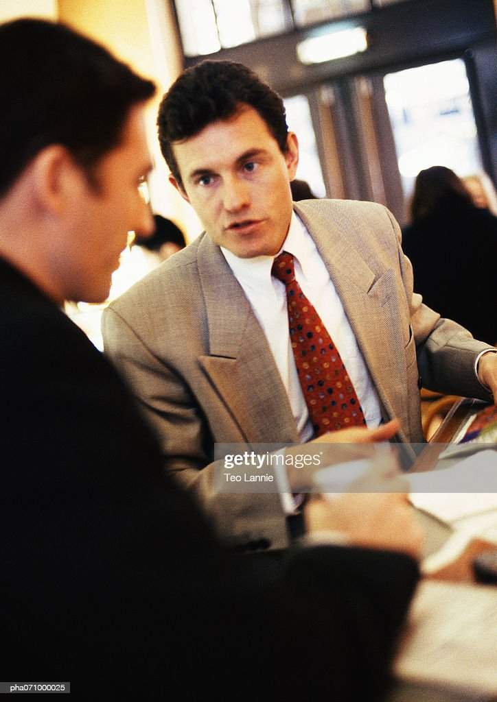 Businessmen talking together, close-up : Stock Photo