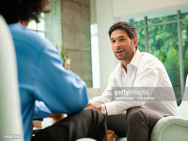 businessmen talking together in lobby - interview stock pictures, royalty-free photos & images