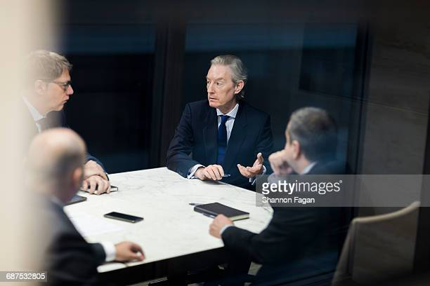 businessmen talking together in office meeting - formal stock pictures, royalty-free photos & images